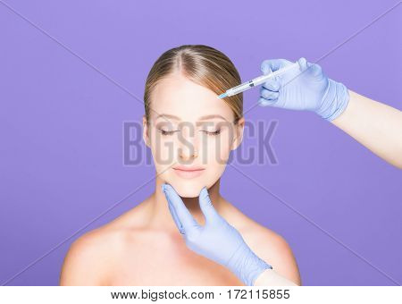 Young and beautiful woman having skin injections over magenta background. Plastic surgery concept.