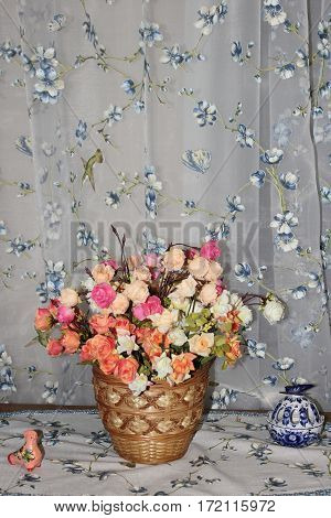 beautiful multi-colored artificial roses in a wicker basket on the background fabric folds with embroidery