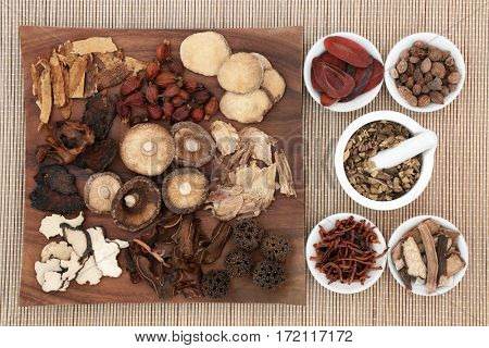 Traditional chinese herb selection used in herbal medicine on maple wood board and in porcelain bowls with mortar and pestle on bamboo.