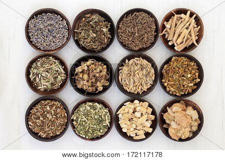 Herbs to help sleeping and anxiety disorders in wooden bowls on distressed white wood background.