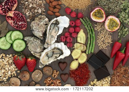 Aphrodisiac food selection for good sexual health on oak wood background.