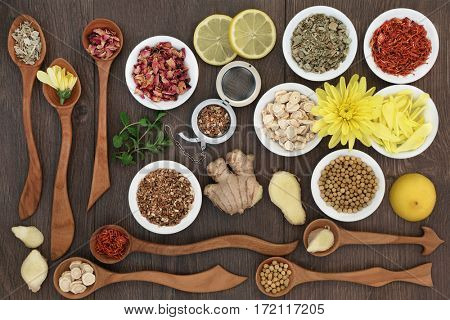 Herbal tea selection used in chinese herbal medicine in wooden spoons, china bowls and loose with strainer on oak background.