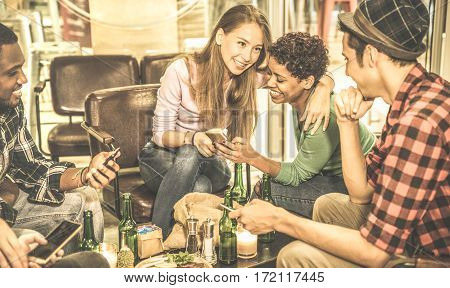 Multiracial friends drinking beer and having fun with mobile phone at cocktail bar restaurant - Friendship concept with people enjoying time out together - Warm retro filter with focus on blond girl