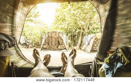 Point of view with couple of legs inside camping tent - Travel wanderlust concept with young people enjoying adventure experience - Blurred edges with soft focus on feet and retro greenery filter