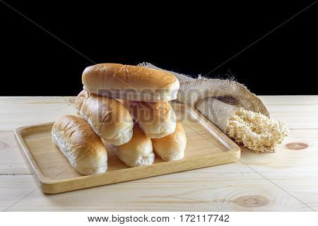 Hotdog buns in wood plate on wooden table isolated on black