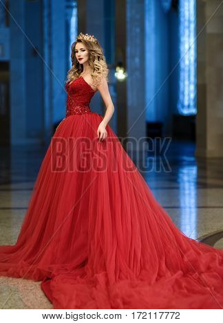 Beautiful Woman In A Red Long Dress And A Golden Crown In The Great Hall