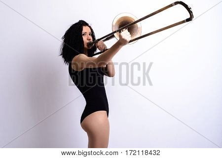 Slender young brunette girl with curly hair in a black bodysuit playing the trombone. Isolated on a white background. Studio shot