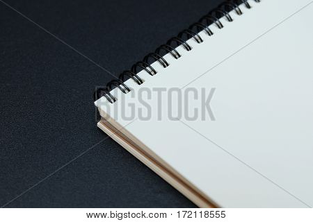 Empty notebook opening on black table background.