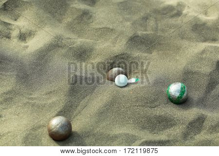Bocce sport balls metal and plastic boules in natural sand on sandy beach outdoors on summer day on grey textured background