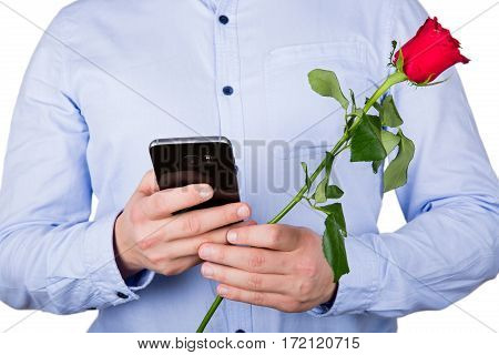 Close up picture of a young guy holding a red rose and texting his girlfriend