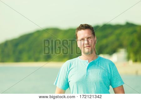 Adventure summer traveling concept. Portrait of handsome guy during summertime wearing blue tshirt