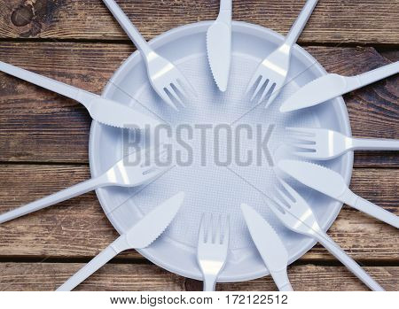 many plastic forks and knives lying on an empty plate.top view.toned