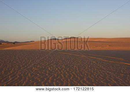 Slope hill sand on yellow dunes on blue sky background. Sustainable ecosystem. Canary island, Fuerteventura