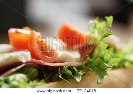 closeup of open sandwich with prosciutto, mozzarella and tomatoes on kitchen table, shallow focus