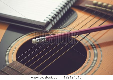 Notebook and pencil on guitar. Writing music conceot.