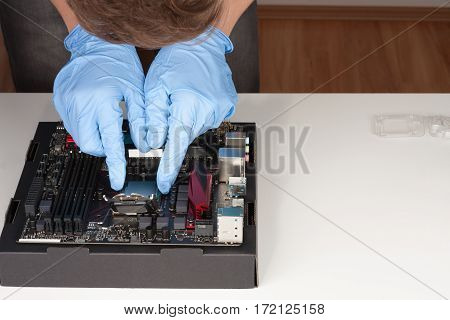 Young Man With Gloves Plug In Cpu On Motherboard Socket