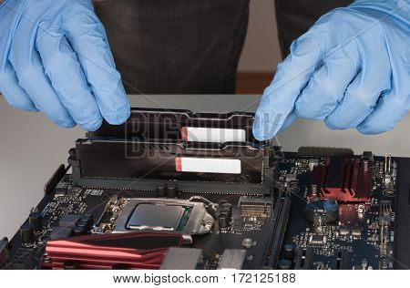 Close Up Of Man Hands With Gloves Installing Ram Ddr4 Memory Module In Slot On Motherboard