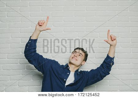 Young happy man triumphing with raised fists against brick wall