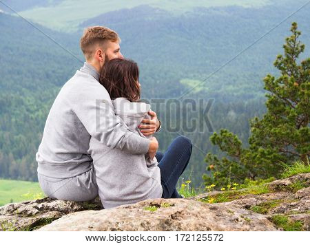 Loving Young Couple Sitting On A Mountain, Hugging And Looking Away, Love And Feelings Concept