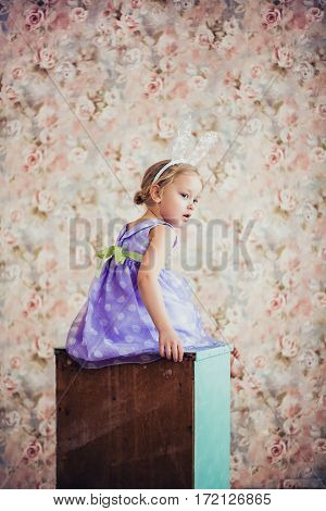 Portrait of a cute little girl with bunny ears. Easter portrait. Floral background.