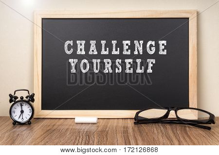 Challenge Yourself word on chalkboard with chalk.