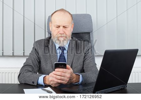 Picture of a stern businessman sending a message by phone