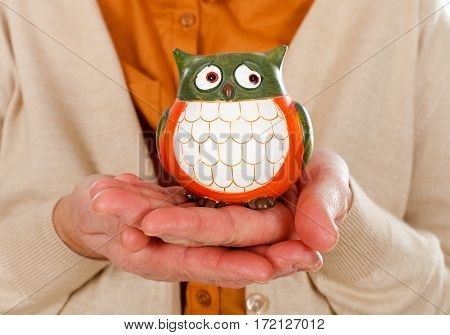 Close up picture of an elderly woman holding an owl as the symbol of wisdom