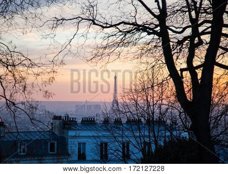 Eiffel Tower seen from Montmartre hill sunset in Paris France.
