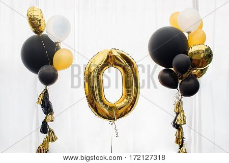 Decoration for Golden number zero balloon, white background, gold and black balloons with tassels