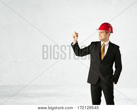 A young architect in red safety helmet planning and drawing with a pen in his hand in empty space in front of a white background.