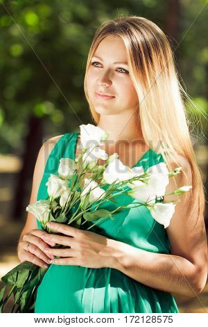 Portrait Of A Blonde Pregnant Woman With Flowers In Their Hands