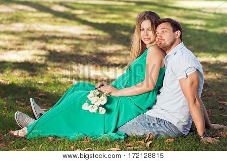 Beautiful young pregnant couple in nature .