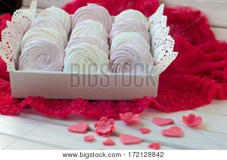 Composition of white and rose zephyr in box lay on red fabric white wooden table near small sweet flower heart figures