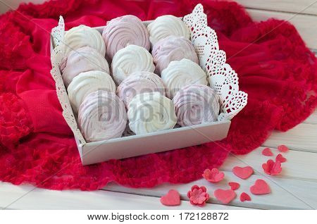 confectionery set. white and rose zephyr lay on wooden table with decorations - serviette red lace fabric small flower heart figures