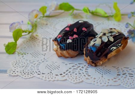 confectionery composition. Two chocolate eclairs lay on white lace serviette near green flower stem on wooden table