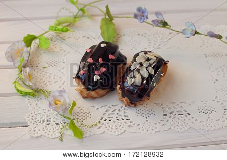 Fresh chocolate eclairs with sprinkles lay on white lace serviette between green stems and flowers on wooden table