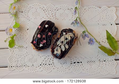 Two delicious dark chocolate eclairs with sprinkles lay on white lace serviette on wooden background between green flower stems. Top view