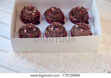 pastry-shop. Box with delicious chocolate cupcakes with rose white small heart sprinkles lay on white serviette on wooden table