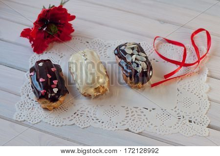 Three delicious decorated eclairs and red poppy flower ribbon lay on lace serviette on wooden table