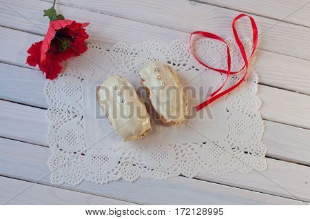 confectionery. Two white chocolate eclairs with silver balls and red poppy flower ribbon lay on serviette on wooden table. Top view