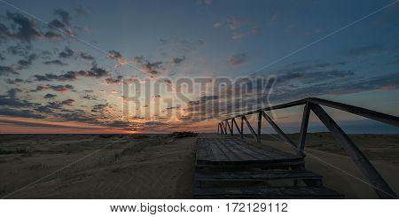 Sunrise over the desert sand. Wooden path leading to the sun. Panorama.