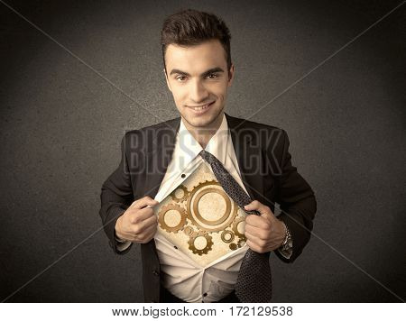 Businessman tearing shirt off and machine cog wheel shows on his chest concept on background