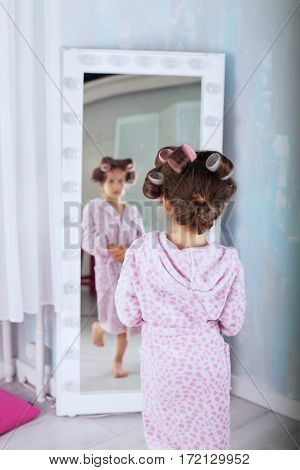 A child in bathrobe and curlers looking in mirror. The concept of fashion and beauty.