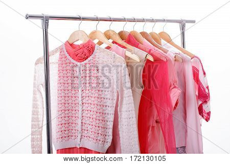 pink womens clothes on wood hangers on rack on white background. closet women dresses, blouses