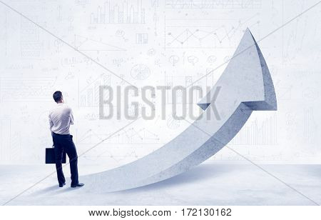Young sales business person in elegant suit standing with his back in front of a big arrow pointing up and a clear background full of pie charts, numbers