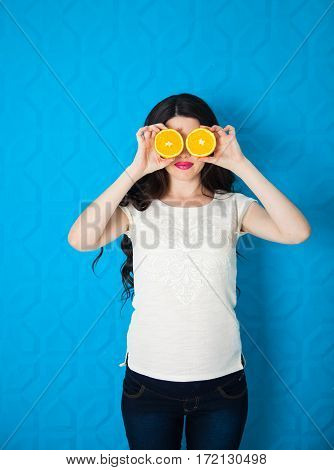 Beautiful Close-up Young Pregnant Woman With Oranges On Blue Background. Healthy Food Concept. Skin