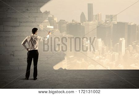 An elegant businessman with a paint roller transforming a brick wall into urban city landscape including tall buildings concept