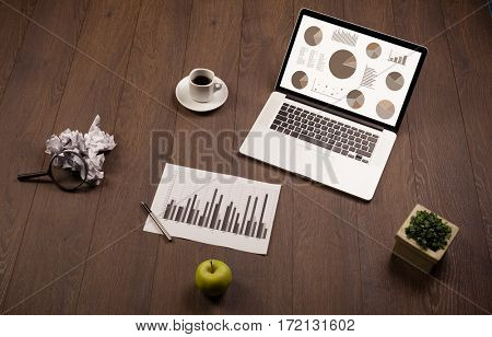 Pie chart graph icons and symbols on laptop screen with office accessories
