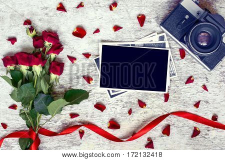 blank photo frame, vintage retro camera and red roses flowers with petals over white rustic wooden background. top view. vintage toning
