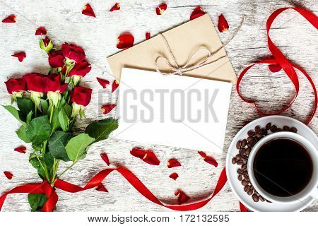 blank white greeting card and envelope with coffee cup and red roses flowers with petals over white rustic table. mock up